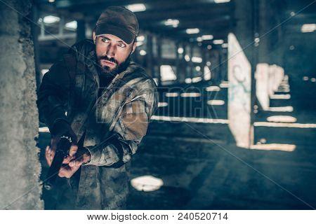 Careful Man Is Looking Straight Forward. He Is Standing Behind Column In A Big Hangar. Warrior Ha A