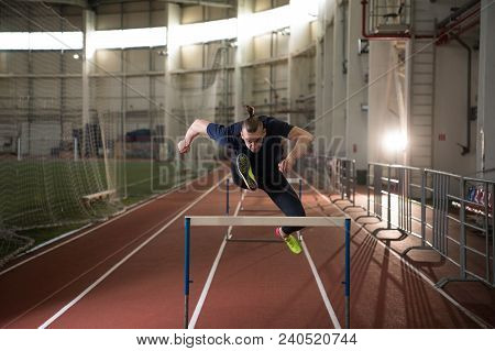 The Shot Of Concentrated Male Track And Field Athlete Jumping Over The Hurdle.indoor Training