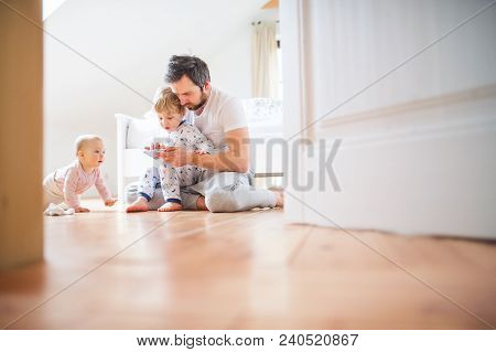 Father And Toddler Children With Smartphone Sitting On The Floor At Home At Bedtime. Paternity Leave