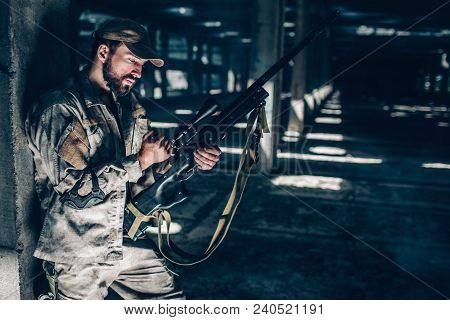Horizontal Picture Of Soldier Standing Very Close To Column With His Back And Recharging Riflle. He