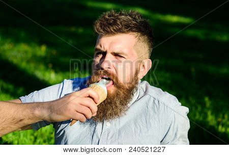 Bearded Man With Ice Cream Cone. Man With Long Beard Eats Ice Cream, While Sits On Grass. Man With B