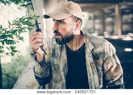 Careful Hireling Is Talking To Portable Radio By Holding It In Right Hand. He Is Looking Straight Fo