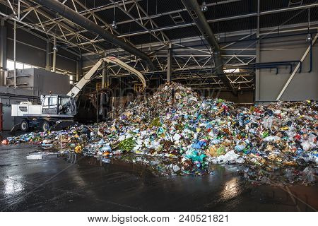 Excavator Sorts Plastic Garbage At Waste Processing Plant. Separate Garbage Collection. Recycling An