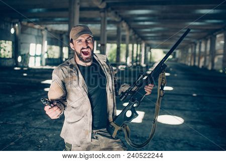 Courageous And Fearless Bearded Man Is Standing And Screaming. He Is Insane. Guy Is Holding Rifle In