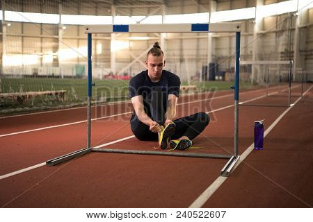 The Shot Of Track And Field Athlete  Tying His Shoelaces Before The Training.indoor Training