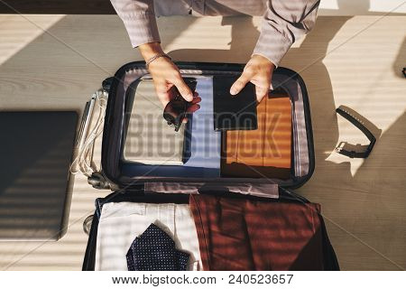 Businessman Preparing For Business Trip.he Is Packing Clothes In Suitcase