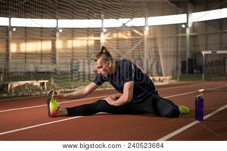 The Shot Of Male Track And Field Athlete Stretching And Relaxing After The Training.