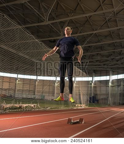 The Shot Of Concentrated Male Track And Field Athlete Warming Up Before Hurdling Training.indoor Tra