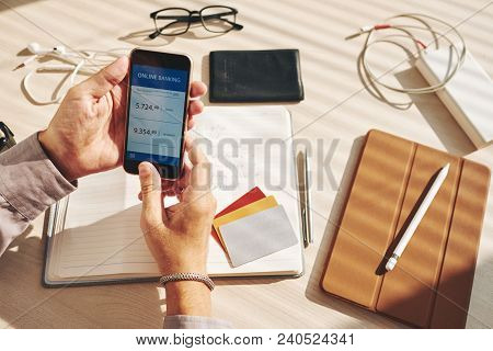 Man Checking An Account In An Online Bank On His Smartphone
