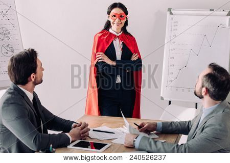 Smiling Super Businesswoman In Mask And Cape With Businessmen In Office