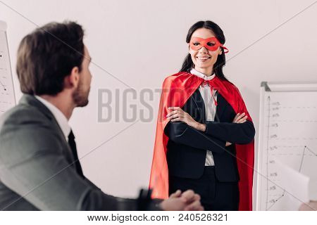 Smiling Super Businesswoman In Mask And Cape Looking At Businessman In Office