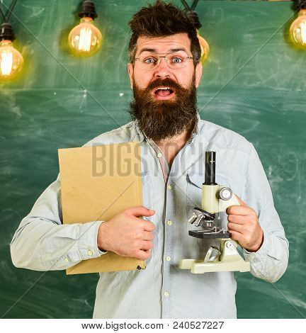 Teacher In Eyeglasses Holds Book And Microscope. Science Concept. Scientist Holds Book And Microscop