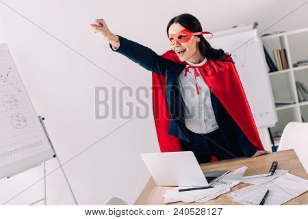Attractive Super Businesswoman In Cape And Mask Screaming And Standing With Hand Up In Office