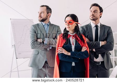 Super Businesswoman Standing With Crossed Arms In Mask And Cape With Businessmen In Office