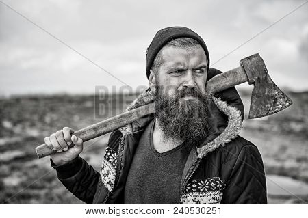 Hipster With Beard And Mustache On Strict Face Carries Axe On Shoulder, Skyline Background. Lumberja