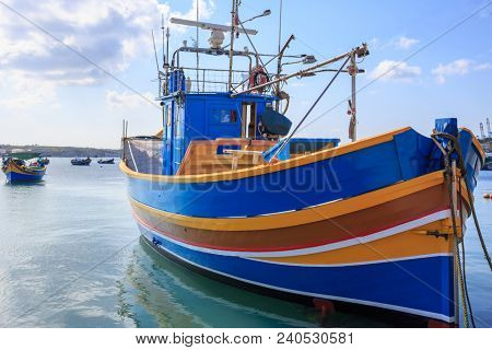 Traditional colorful fishing boat, luzzu, anchored at Marsaxlokk, the historic port of Malta. Blue sky with clouds and village background. Close up view with details.