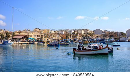 Marsaxlokk historic harbor full of boats in Malta. Blue sky and village background. Destination for vacation, relaxing and fishing.