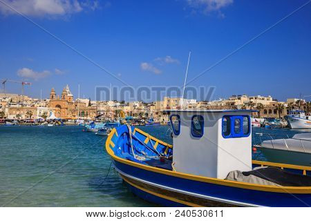 Traditional colorful fishing boats, luzzu, anchored at Marsaxlokk, the historic port of Malta. Blue sky and village background. Close up view.