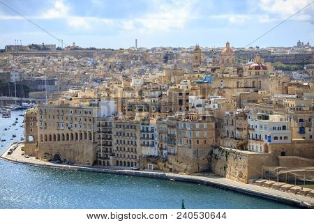 Malta, Valletta. Senglea, a fortified grand harbour that is surrounded of boats and ships, under a blue sky with few clouds. Panoramic view.