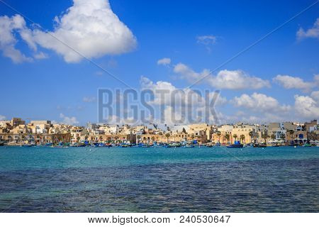 Marsaxlokk historic port full of boats in Malta. Blue sky with few white clouds and village background. Destination for vacation, relaxing and fishing. Panoramic view.