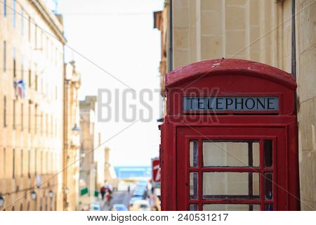 Traditional red British telephone booth. Blank, old, peeled phone box in Valletta, Malta. Space for text, close up view, blurred town background.