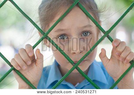 Sad Girl Behind The Bars. Sad Blured School Girl Behind Bars. Parenting,