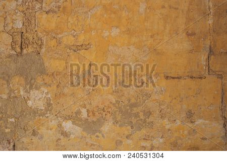 Weathered yellow painted wall background, partially faded. Corroded, peeled, vintage, blank wall for backdrop. Close up view with details.