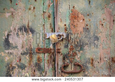Wooden peeled door background locked with rusty handle and padlock. Timeworn brown, green entrance provides safety and privacy. Close up view with details.
