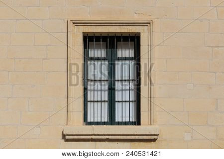 Malta, Valletta. Facade of yellow limestone house with closed window with metal grid, that provides security. Close up view.