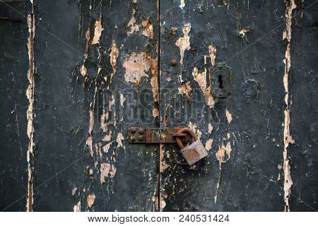 Wooden dark grey door background locked with rusty padlock. Timeworn entrance provides safety and privacy. Close up view with details.
