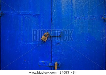 Wooden blue door background locked with two rusty padlocks. Old, closed entrance provides safety and privacy. Close up view with details.