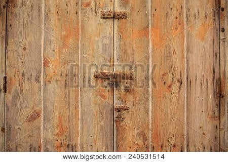 Wooden brown door background locked with rusty padlock. Timeworn, closed entrance provides safety and privacy. Close up view with details.