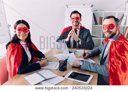 Smiling Super Businesspeople In Masks And Capes Sitting At Table In Office