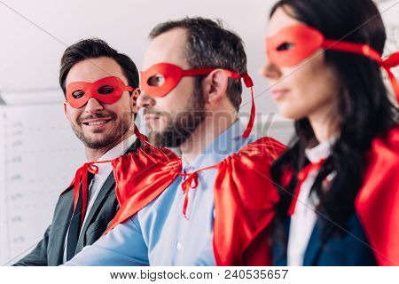 Side View Of Smiling Super Businesspeople In Masks And Capes Looking Away In Office