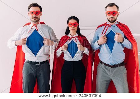 Serious Super Businesspeople In Masks And Capes Showing Blue Shirts In Office