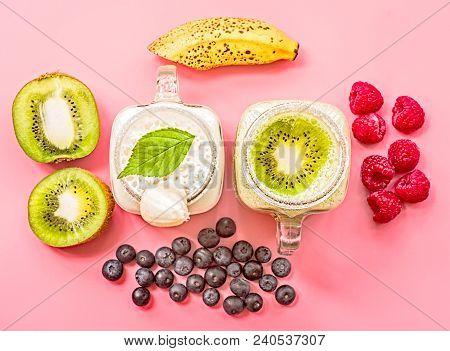 Two Banana And Kiwi Milkshakes In Mason Jars With Creme On Top Decorated With Kiwis, Bananas, Raspbe