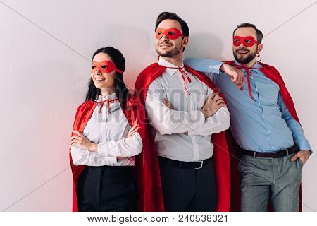 Smiling Super Businesspeople In Masks And Capes Looking Away Isolated On White
