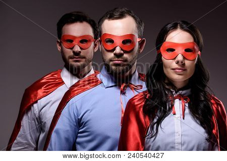 Super Businesspeople In Masks And Capes Looking At Camera Isolated On Grey