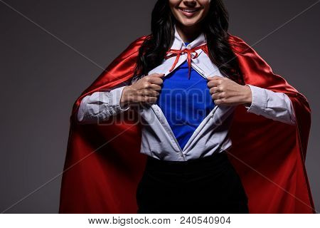 Cropped Image Of Super Businesswoman In Red Cape Showing Blue Shirt Isolated On Black