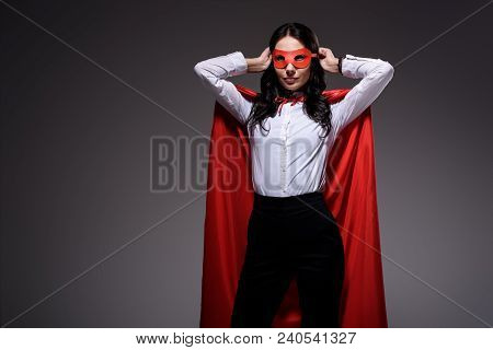 Attractive Super Businesswoman In Red Cape Tying Mask Isolated On Black