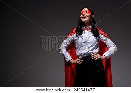 Smiling Attractive Super Businesswoman In Red Cape And Mask Isolated On Black