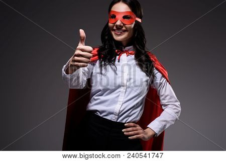 Attractive Super Businesswoman In Red Cape And Mask Showing Thumb Up Isolated On Black