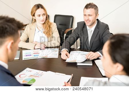 Portrait Of Business People Sitting In Circle At Meeting Table In Conference Room Discussing Work An