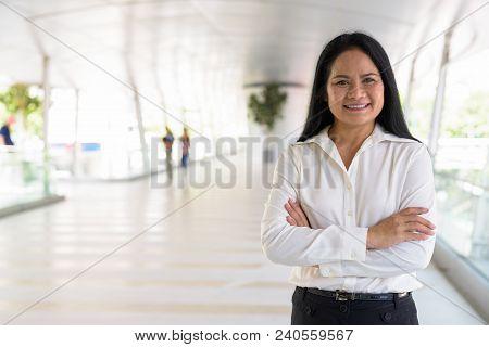 Portrait Of Mature Beautiful Asian Businesswoman Relaxing At The Footbridge In The City Of Bangkok,