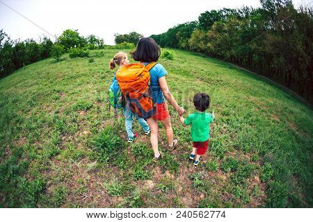 A Woman With Children Goes Hiking. Traveling With Family. The Boy Walks With His Brother And Mother