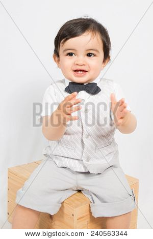A Boy In A Shirt And Bow Tie Sit On Box Ready To Applaud