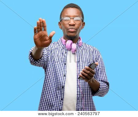 African black man student with smartphone annoyed with bad attitude making stop sign with hand, saying no, expressing security, defense or restriction, maybe pushing