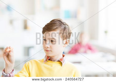 Handsome schoolboy with piece of chalk standing by board, thinking of idea and making notes