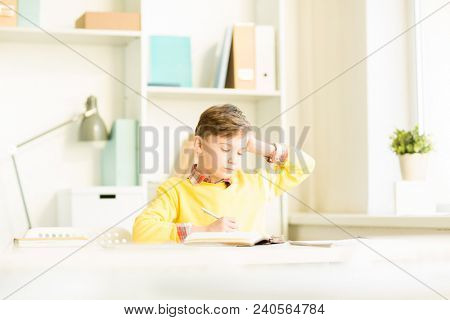 Clever young schoolboy sitting by desk in classroom, reading his notes and thinking of new ideas