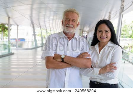 Portrait Of Mature Multi-ethnic Couple Relaxing Together At The Footbridge In Bangkok, Thailand